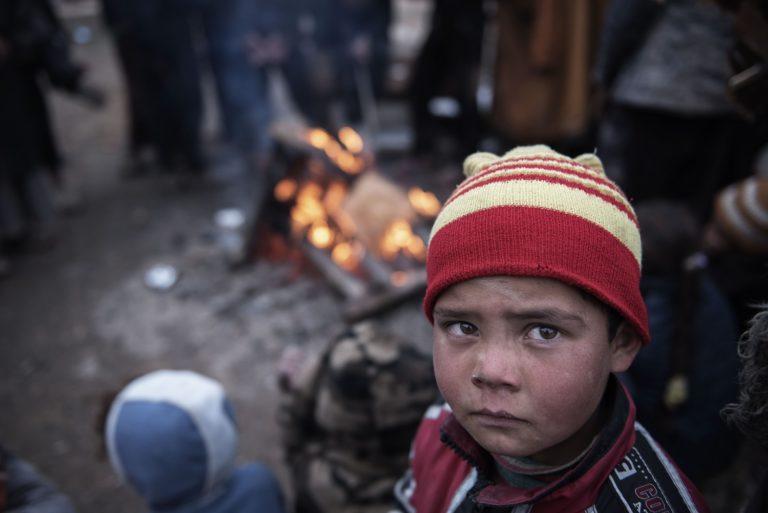 En flygtningedreng står foran et varmende bål efter han er flygtet fra kampene mellem ISIS og Irakiske styrker.
