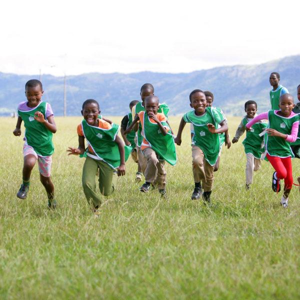 Børn løber og en grøn mark i Lobamba, Afrika