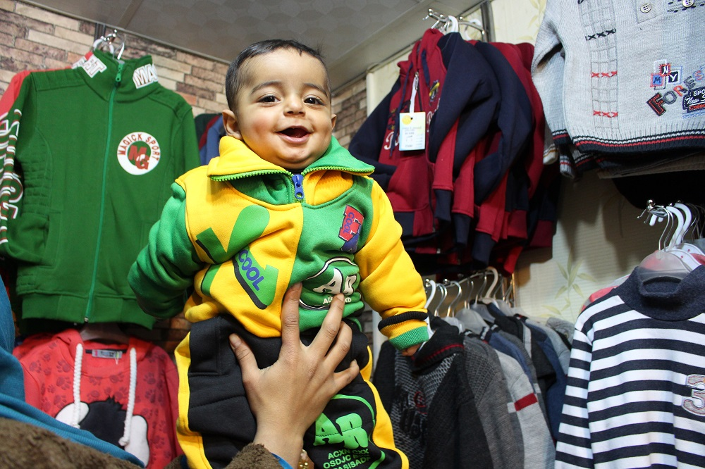 Igen i år kæmper vi for vinterhjælp til Syriens børn. Sammen med vores støtter vil vi sikre vinterhjælp til over 1,5 mio. af de allermest udsatte børn denne vinter. Khaled på 1 år får her varmt vintertøj, som hans mor betaler med en UNICEF-voucher.