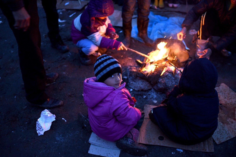 Flygtninge varmer sig ved et bål i Macedonien