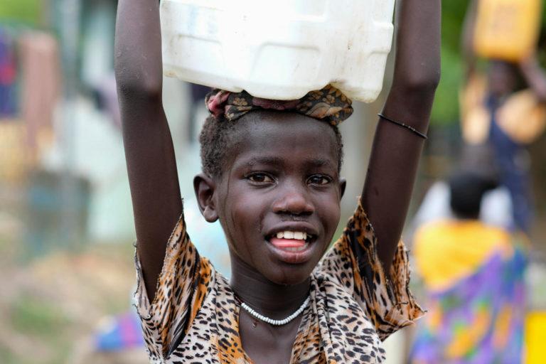 Sandy Chuol er på vej hjem med en dunk vand, som hun har hentet på det UNICEF-støttede vandpunkt i Malakal, Sydsudan. Byens vandsystem blev ødelagt af krigen, og 80.000 mennesker stod uden rent vand, indtil vandpunktet blev oprettet.