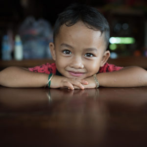 dreng der læner sig op ad at bord. Han deltager i et studie i udsatte områder. Om UNICEF.