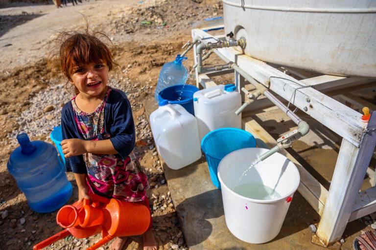 3-årige Sahira henter rent vand fra en UNICEF-vandtank i Irak.