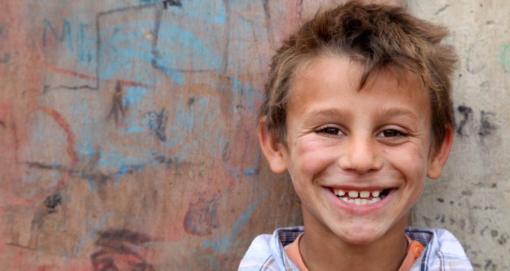 En smilende dreng på gaden i Pristina, Kosovo