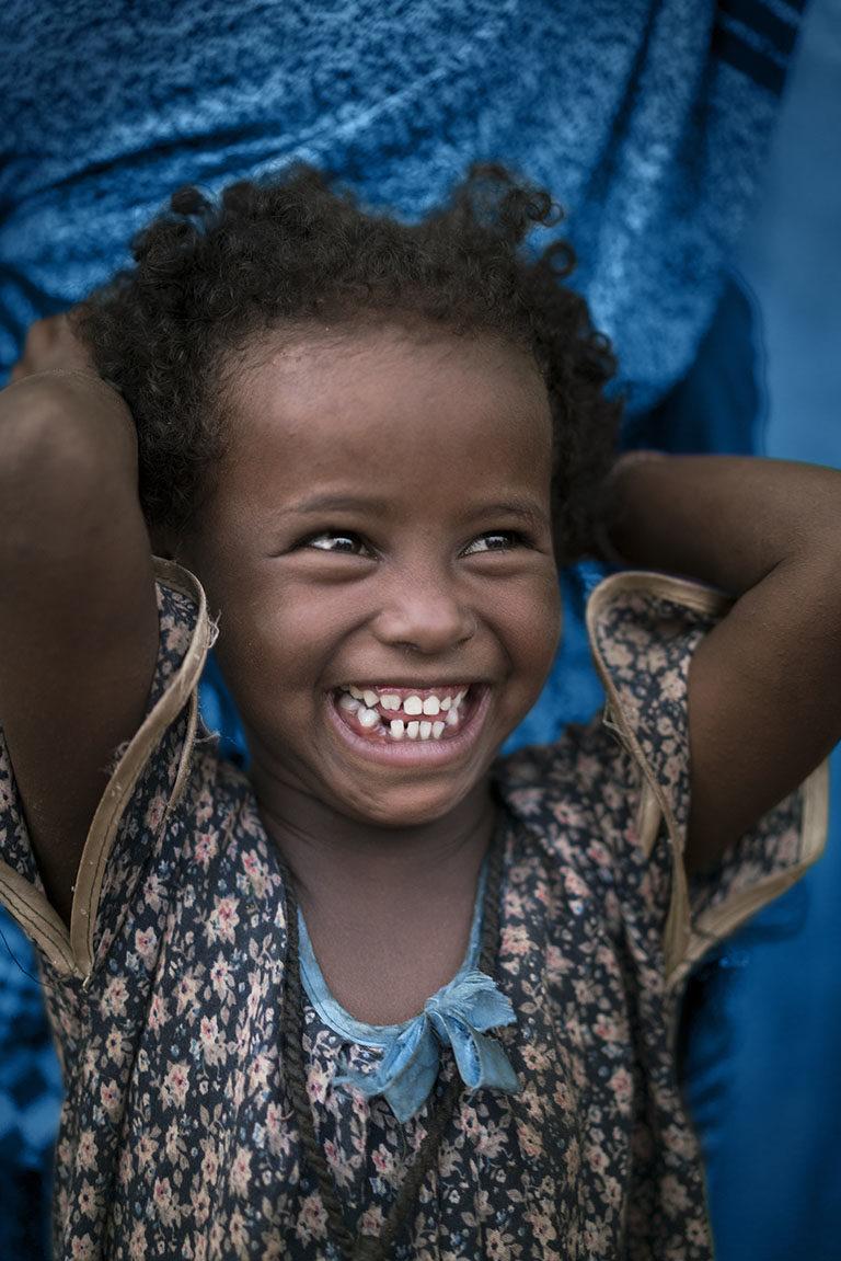 En Etiopisk pige smiler - du kan hjælpe børn ved at indskrive unicef i dit testamente