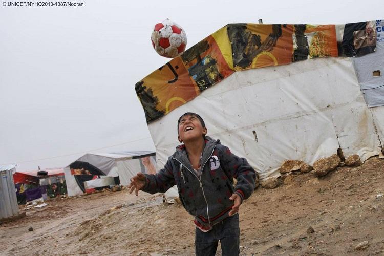 Dreng leger med en fodbold i en flygtninge lejr