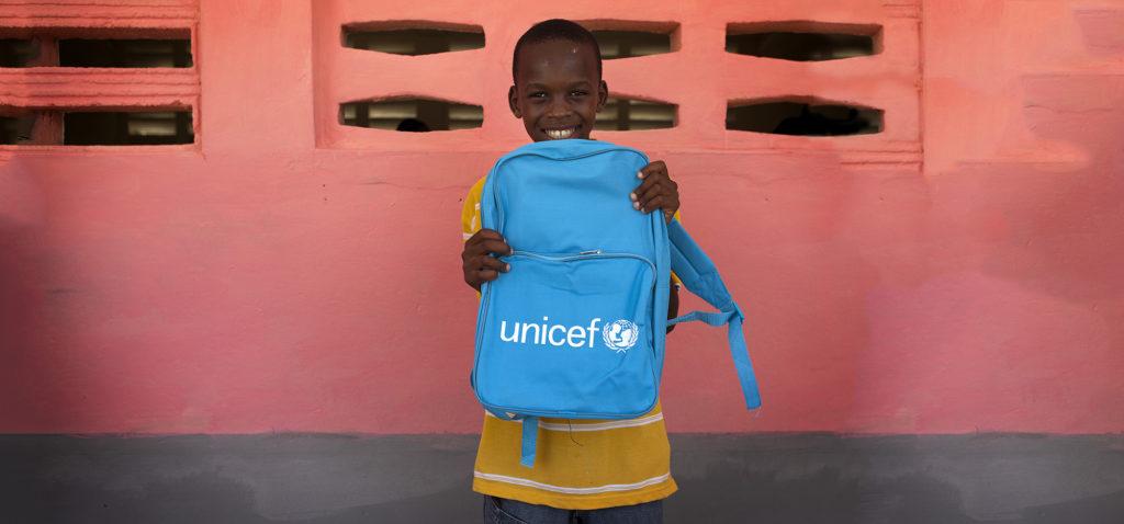 En dreng viser stolt sin unicef skoletaske frem -Sådan hjælper vi børn i skole