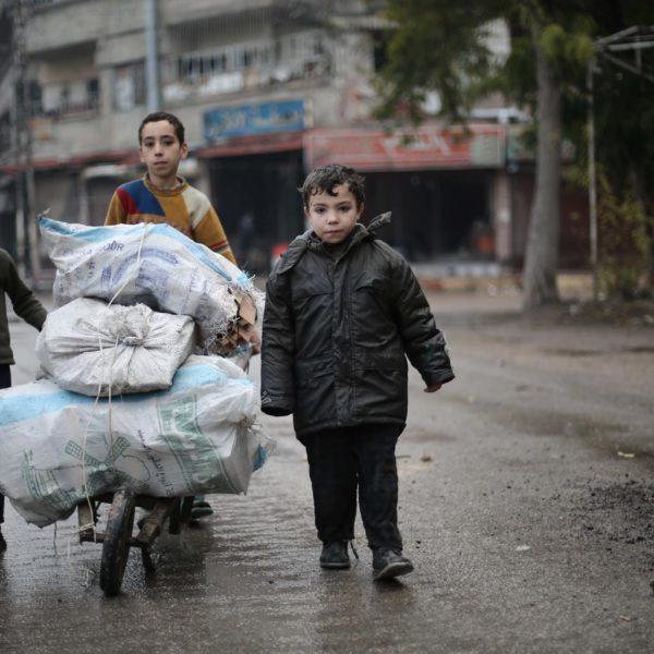 Tre børn går på gade i Ghouta Syrien med et stort læs brænde på en trillebørge