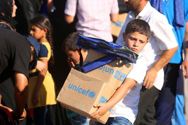 En syrisk dreng har netop modtaget nødhjælp fra UNICEF i form af en skoletaske og hygiejneforsyninger.