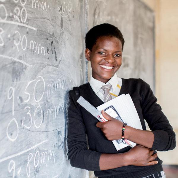 En ung pige læner sig op ad klassens tarvle