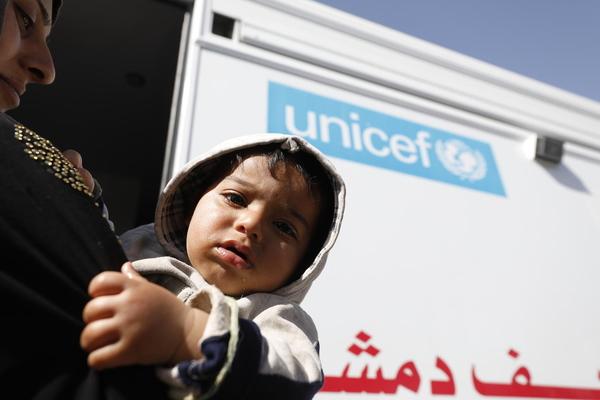 En lille dreng er sammen med sin mor på vej ind i en UNICEF-støttet mobil sundhedsklinik i Adra, Syrien.