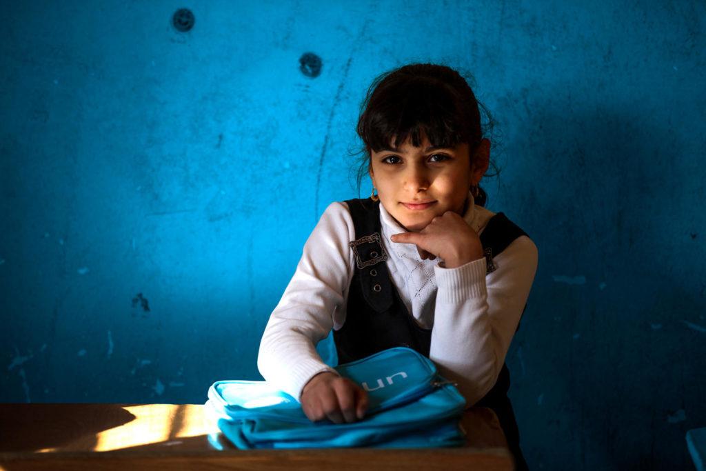 8-årige Janna fra Baghdad sidder i et klasseværelse med sin nye UNICEF skoletaske. UNICEF kæmper for at alle børn kan lære og uddanne sig.