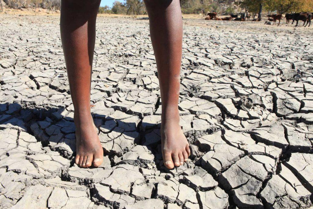 17-årige Vanessa står i en udtørret dam, hvor hun plejer at hente vand i Siyephi landsbyen i Zimbabwe.