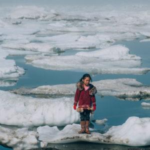 En pige fra et oprindeligt folk står på en isflage i det arktiske område i Nordamerika. Global opvarmning smelter isen og truer de oprindelige folks overlevelsesmuligheder og levevis. Hendes folk er afhængige af en bæredygtig verden.