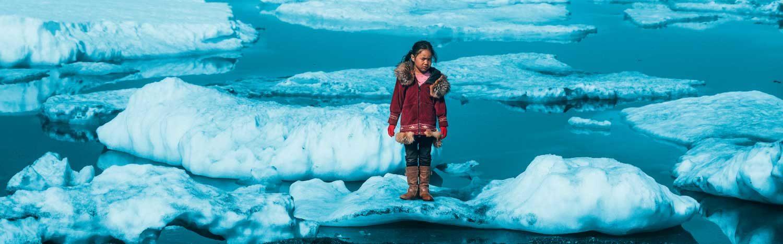 En pige fra et oprindeligt folk står på en isflage i det arktiske område i Nordamerika. Global opvarmning smelter isen og truer de oprindelige folks overlevelsesmuligheder og levevis.