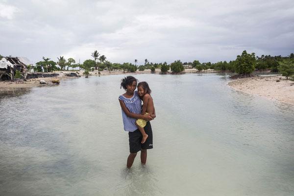16-årige Taronga fra Kiribati må bære sin to-årige lillesøster, fordi deres landsby er oversvømmet.