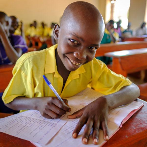 En dreng smiler til kameraet i sin skoleklasse i en skole i Uganda