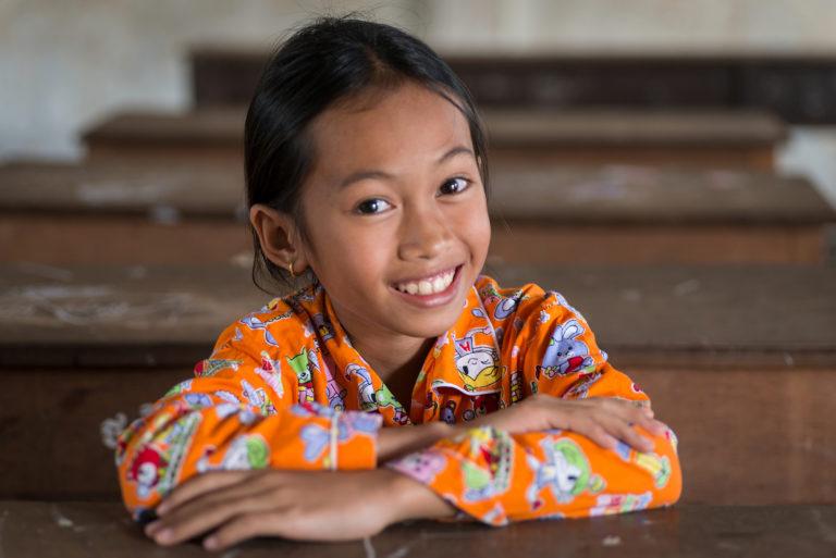 UNICEF arbejder for at sikre børns rettigheder til uddannelse i samarbejde med de enkelte landes regeringer. Her ses en pige fra Cambodia, der er glad for at kunne gå i skole.