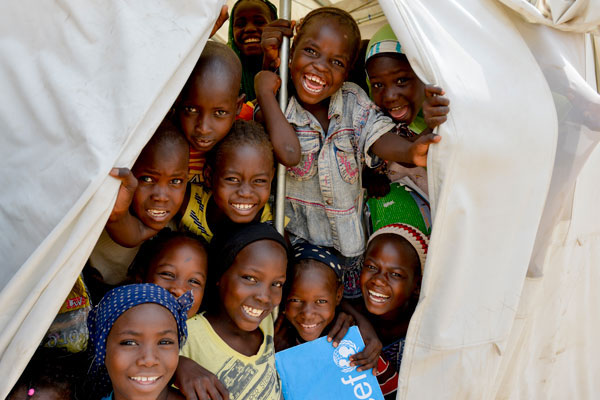 En gruppe glade elever står i indgangen til det nødhjælpstelt, som lige nu udgør deres skole i Yola, Nigeria. Børnene er internt fordrevne og er kommet tilbage i skole med hjælp fra UNICEF.