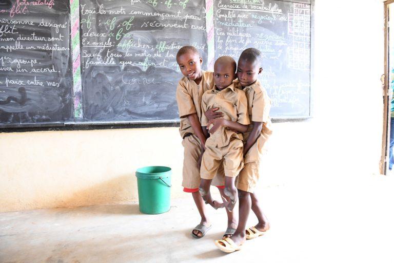 Adama bliver båret på plads af sine skolekammerater. Han går i skole ligesom andre børn, selvom han har et alvorligt handikap.© UNICEF/UN0149801/DEJONGH
