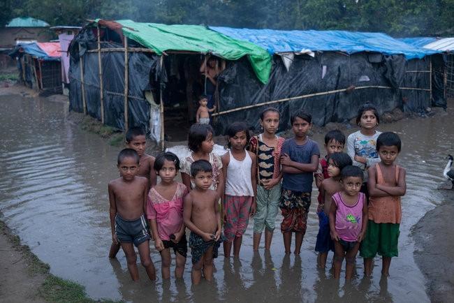 Rohingya-flygtningebørn står i dybt vand, der omringer deres familiers midlertidige hjem i Shamlapur flygtningelejren i Cox's Bazar i Bangladesh.