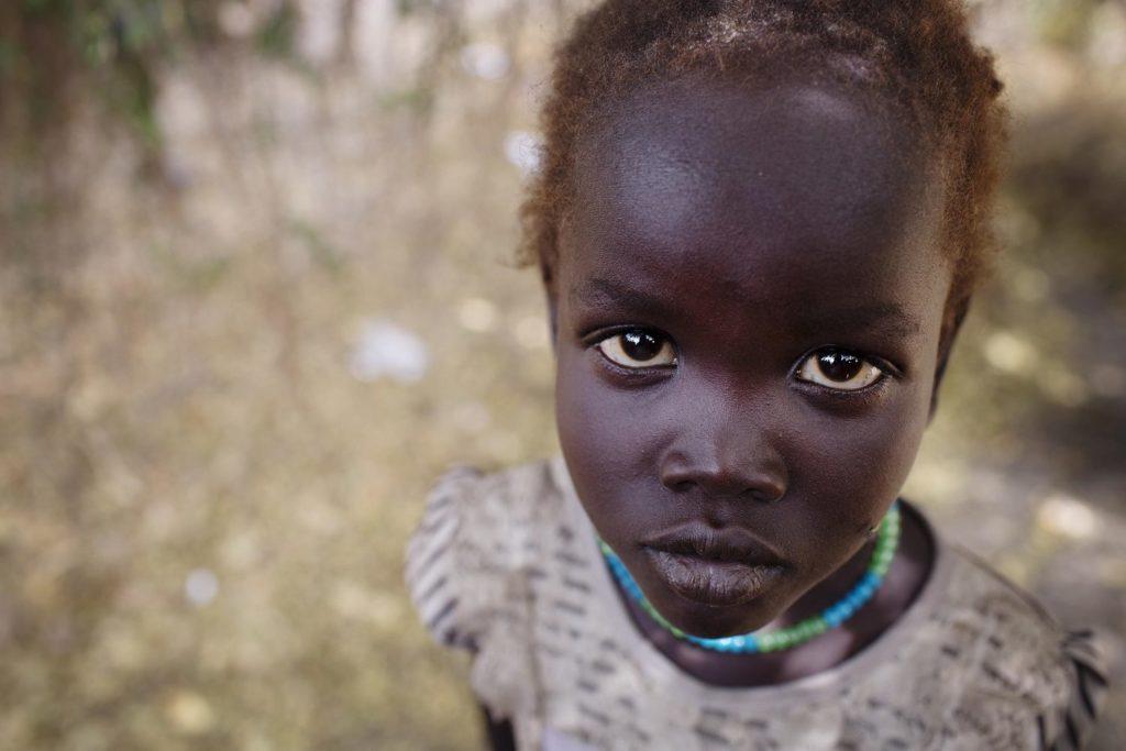 En pige fra Sydsudan kigger ind i kameraet