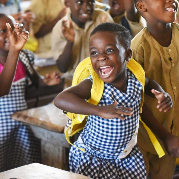 Lille skolepige fra Elfenbenskysten viser sin glæde og entusiasme.