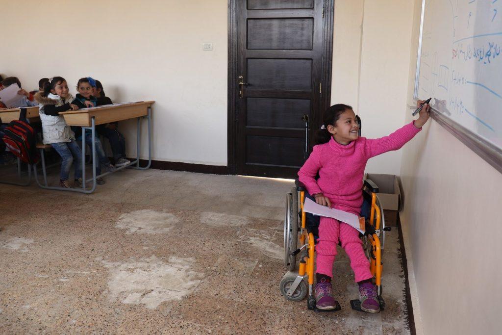 Krigsskadet pige i rullestol skriver på tavlen