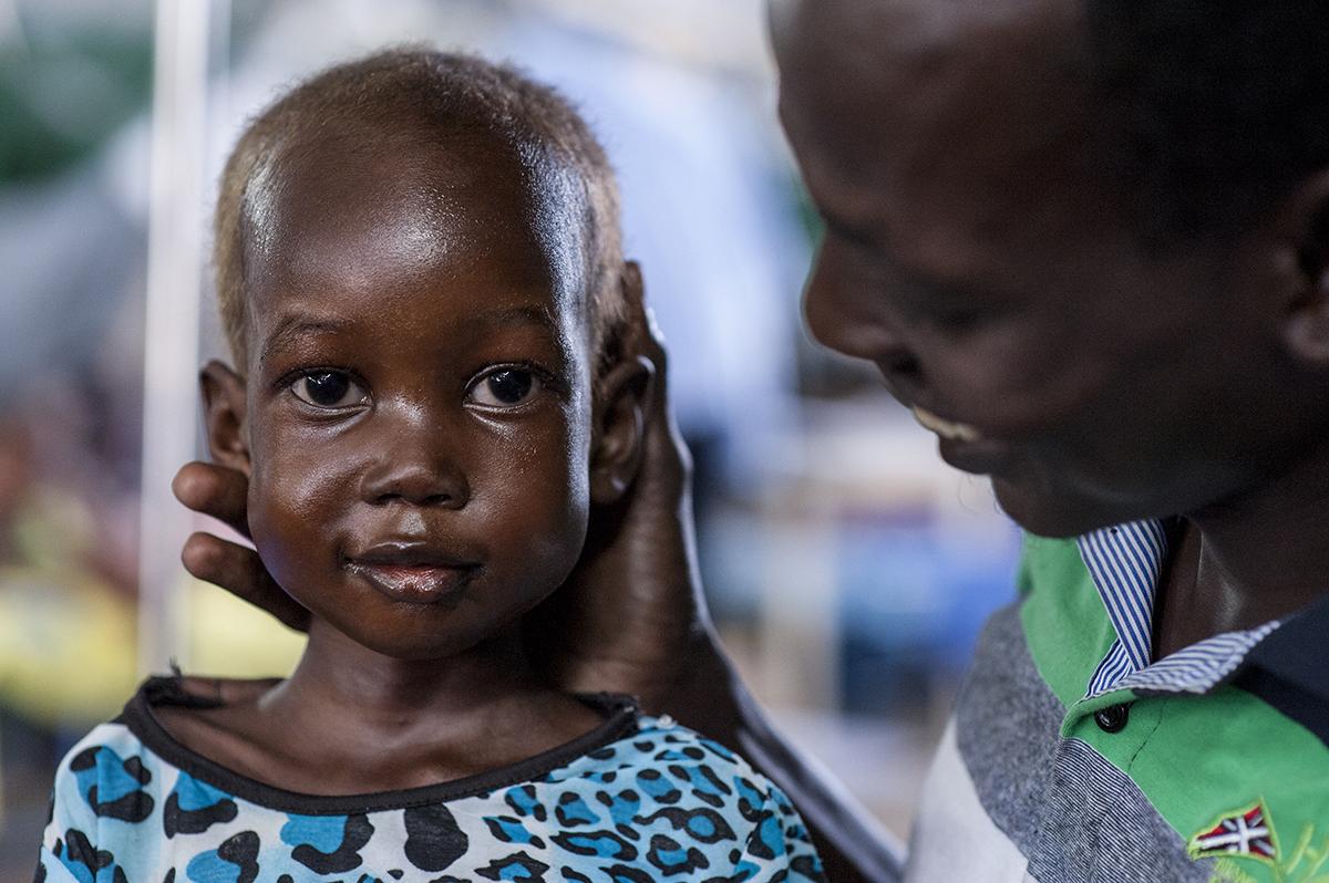 """Allerede på tredjedagen har Nyajime det bedre. Hun kan sidde op og mestrer antydningen af et smil. """"Da vi kom, kunne hun ikke røre sig. Hun kunne ikke gå eller sidde,"""" siger den rørte far. © UNICEF/UNI201744/Rich"""