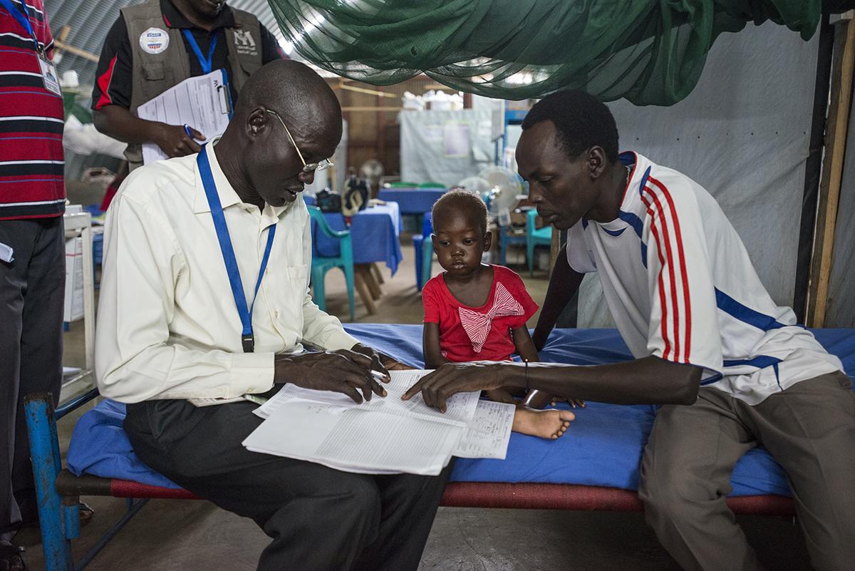 Dag 11. Nyajime bliver stærkere for hver dag. Lægen og hendes far følger kurven nøje, mens Nyajime opmærksomt lytter efter. © UNICEF/UNI201751/Rich