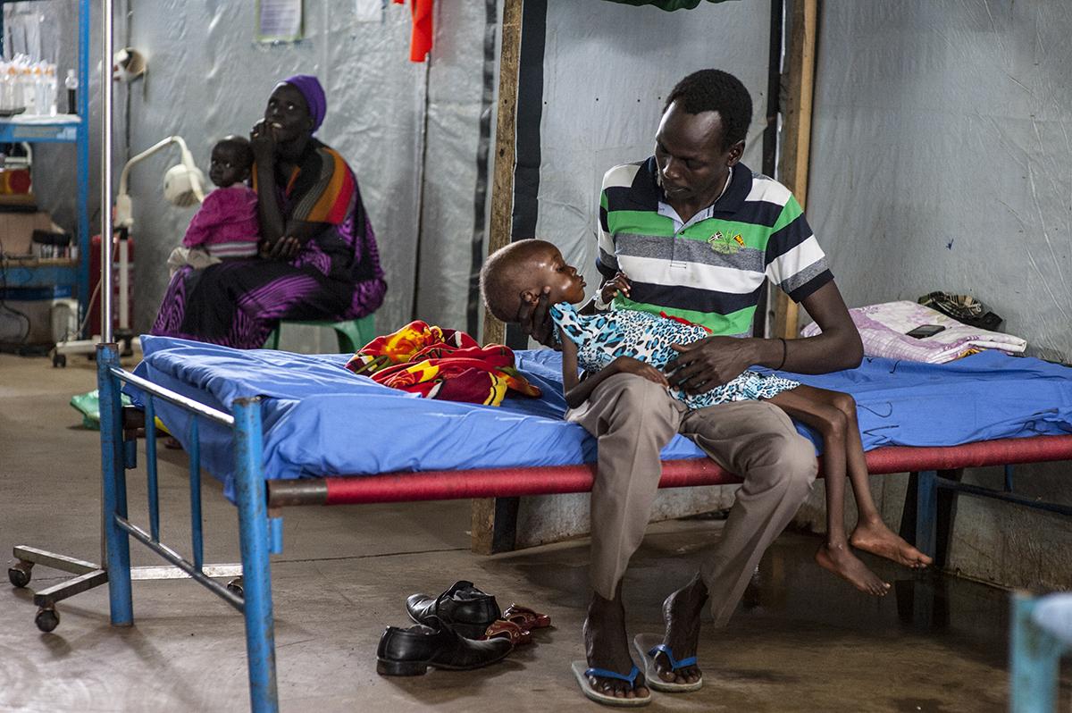 Nyajime er for svag til at sidde op, så hun bliver støttet af sin far, Michael. © UNICEF/UNI201742/Rich