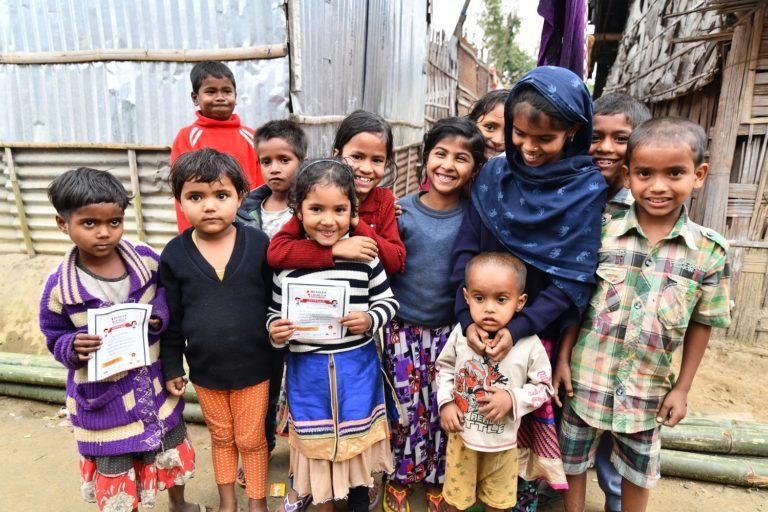 Børn viser deres vaccinationskort frem. Nu er de beskyttede mod livsfarlig mæslinger og røde hunde. © UNICEF/UN0200157/Boro