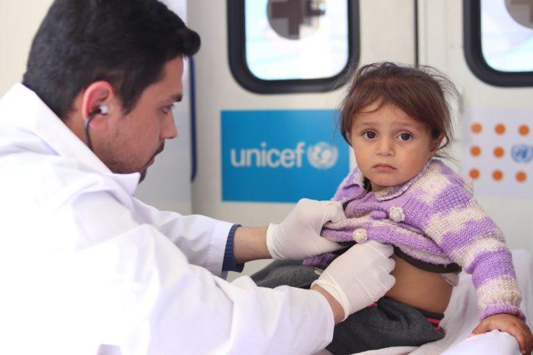 En lille pige undersøges af en læge i Syrien