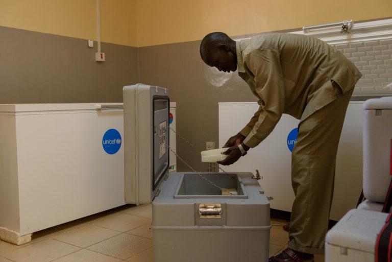 En mand pakker vacciner i et transportabelt køleskab