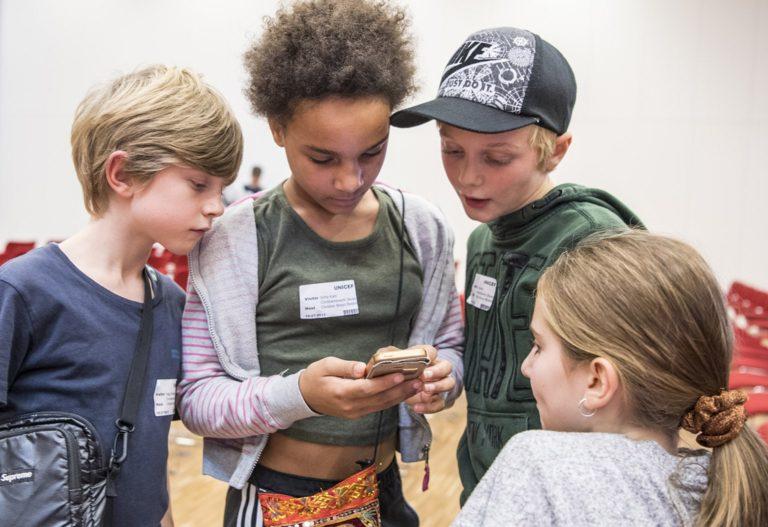 En gruppe børn står omkring en smartphone