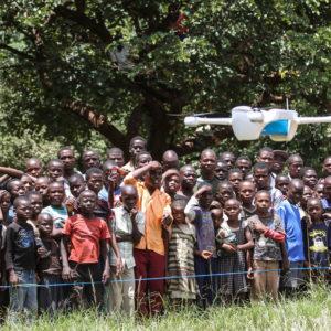 Børn i Malawi følger nysgerrigt med, da UNICEF tester brug af droner i hjælpearbejdet.