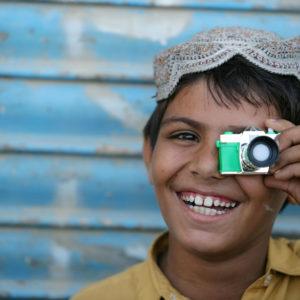En pakistansk dreng leger med et kamera