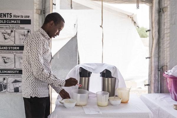 """Lewine Koyoumtan, læge på Ernærings- og rehabiliteringsenheden i Liwa. På billedet er han ved at forberede en terapeutisk mælk til de børn, der er indlagt på stedet. """"Vi modtager cirka 30 børn om måneden. 75 procent kommer fra fordrevne områder. De bliver alle bragt hertil med vores mobile klinikker. De kan ikke komme hertil på andre måder. Dødeligheden på Ernærings- og rehabiliteringsenheden er på otte procent – langt størstedelen kommer sig efter syv til ti dage. Nogle gange kommer børnene for sent, eller også kræver de en form for behandling, vi ikke har mulighed for at give dem."""
