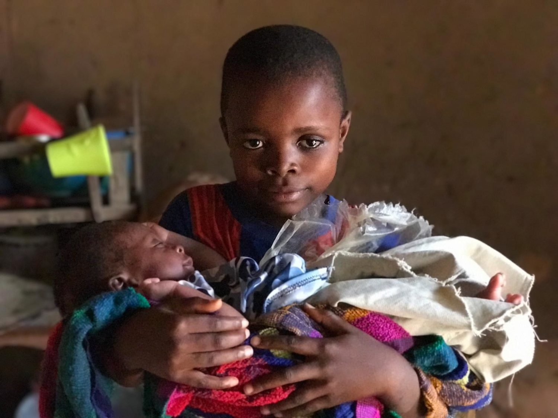 Tshitembda på 9 år holder sin lillesøster i favnen.