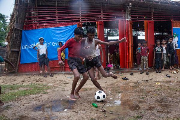 Rohingya børn spiller fodbold foran et børnevenligt område i en flygtningelejr i Cox's Bazaar, Bangladesh.