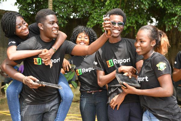 En flok unge i Abidjan, Elfenbenskysten er klar med mobiltelefonen i forbindelse med lanceringen af UNICEFs digitale platform U-Report