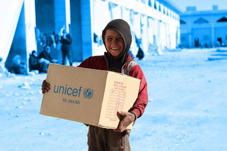 En dreng holder en nødhjælpspakke fra unicef i favnen.