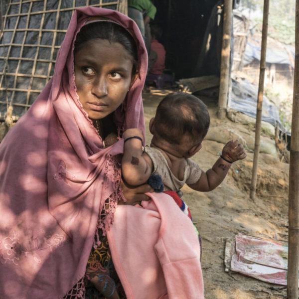 Rohingyaerne - Et folk på flugt: 14-årige Asmot Ara holder sin to måneder gamle baby, Rubina, uden for sin hytte i Balukhali-lejren i Cox' Bazar, Bangladesh. Asmot flygtede fra Myanmar sammen med andre rohingyaer efter hendes landsby blev angrebet i 2016. Under flugten mistede hun sine søskende og forældre af syne, og hun ved ikke, om de overlevede angrebet. Med hjælp fra andre landsbyboere nåede hun til Bangladesh, og hurtigt efter blev hun gift med sine naboers søn. Asmot gik med til ægteskabet, fordi hun var alene i flygtningelejren og fordi familien lovede at tage sig af hende. Kort efter ægteskabet blev hun gravid og fødte lille Rubina. Hun ville nok ikke have giftet sig i så ung en alder, hvis ikke hun var blevet forældreløs og tvunget til at flygte fra sit hjem, tror hun. Hun har meget ansvar nu, som en ung mor og hustru, og hun anerkender, at hun ikke længere er et barn, selvom hun kun er 14 år gammel. Hun tror ikke, at hendes forældre ville være glade for det liv, hun lever nu, men hun synes ikke, at hun havde noget valg som en lille pige et fremmed sted.© UNICEF/UN0156992/Bindra.