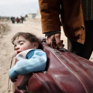 En syrisk man bærer sit lille sovende barn i en kuffert under flugt fra kampene i Øst Ghouta.