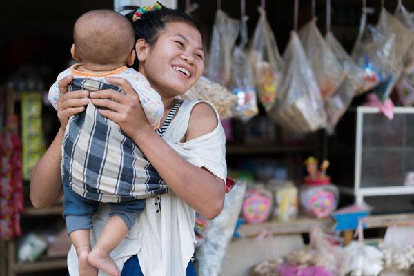 25-årige Vandy fra Laos løfter sin 5 måneder gamle søn i Sen Xay landsbyen