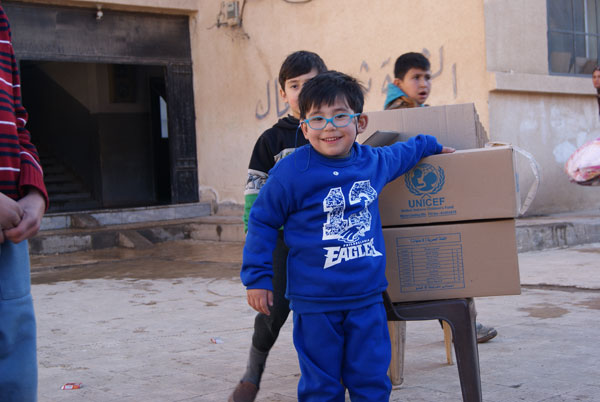 5-årige Mousa viser glad sit nye vintertøj, som han har fået af UNICEF.