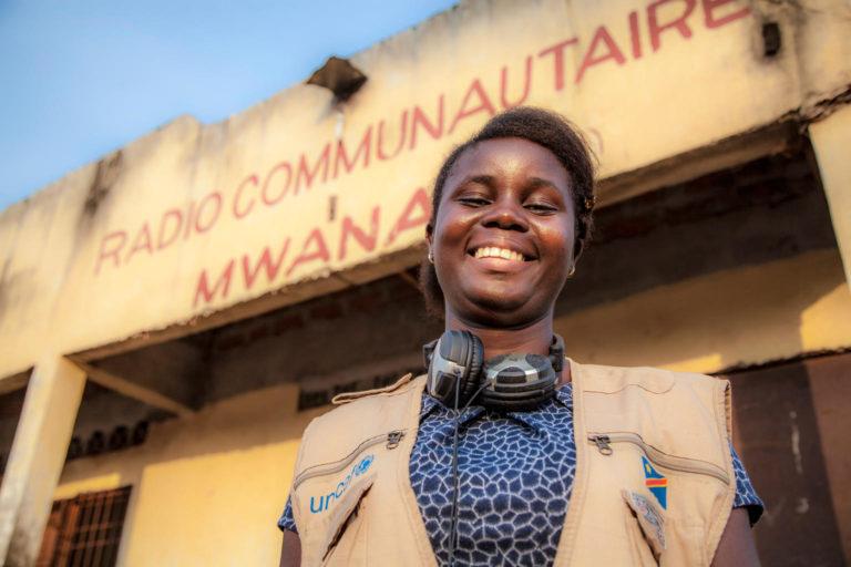 17-årige Hornelie Mpiko, som er UNICEF-støttet radiojournalist i Mbandaka, Congo, smiler foran sin radiostation. UNICEF har uddannet Hornelie og 29 andre unge reportere som sundhedsambassadører, så de kan sprede vigtig viden om god hygiejne i lokalsamfundene.