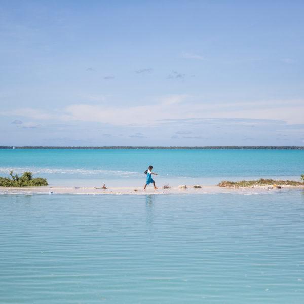 En dreng går hjem fra skole på stranden, hans ø er påvirket af klimaforandringer og vandet står højt