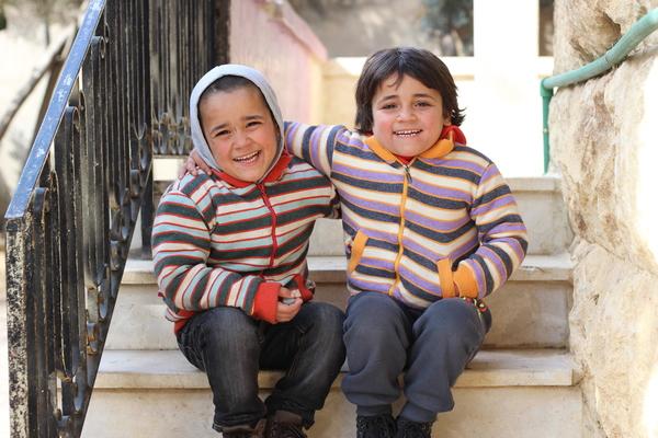 6-årige Zakariya og 5-årige Doha smiler stort uden for deres nye hjem i Aleppo, som UNICEF har givet dem. Zakariya og Doha hører til de mange syriske børn, som er blevet væk fra eller har mistet deres forældre under krigen. Det UNICEF-støttede børnehjem kan huse 74 børn, som går i skole, får traumehjælp og omsorg.