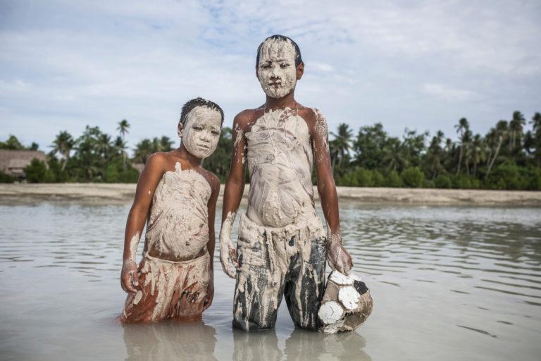 7-årige Tebuaka og 9-årige Teniou står smurt ind i mudder i deres oversvømmede landsby Tebunginako i Kiribati